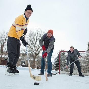 Image of three men playing hockey on an outdoor ice rink