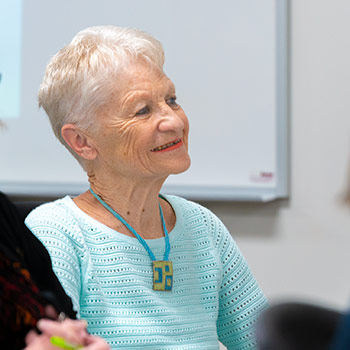 Image of older female student listening to a lecture.